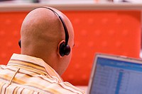 Rear view of a male customer service representative wearing a headset sitting in front of a laptop