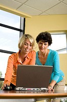 Two businesswomen standing in front of a laptop