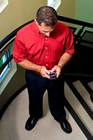 High angle view of a businessman standing on stairs holding a mobile phone