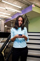 Businesswoman standing on steps working on a palmtop
