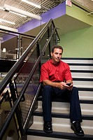 Portrait of a businessman sitting on stairs holding a mobile phone