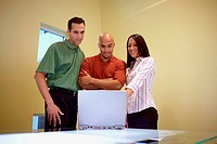Two businessmen and a businesswoman standing in front of a laptop