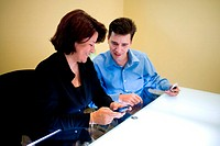 Businesswoman and a businessman sitting in an office looking at a palmtop