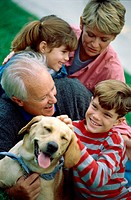 Grandparents with their grandson and granddaughter holding their dog