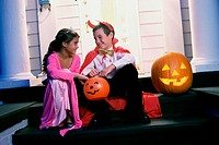 Boy and a girl dressed in Halloween costumes
