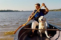 Mid adult man in a row boat with his dog