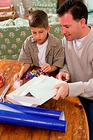 Father and son wrapping a gift