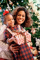 Girl holding a Christmas present and smiling with her mother