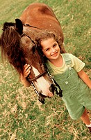 High angle view of a girl standing with a horse