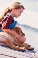 Side profile of a girl sitting with her dog