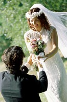 High angle view of a groom giving a bouquet of flowers to his bride