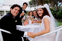 Portrait of a newlywed couple and their friends toasting with champagne glasses
