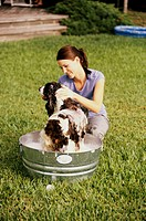 Young woman bathing her dog in a tub