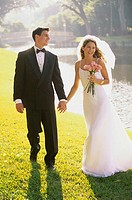 Newlywed couple walking together holding hands