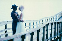 Newlywed couple embracing each other on a pier
