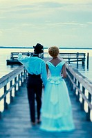 Rear view of a newlywed couple walking on a pier