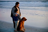 Father and his son with their dog on the beach