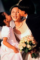 Flower girl and ring bearer kissing a bride