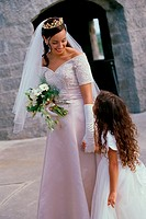 Bride holding a bouquet of flowers talking to a flower girl