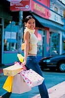 Portrait of a young woman walking with shopping bags