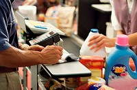 Mid section view of a man and a woman at a checkout counter in a supermarket