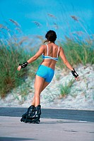 Rear view of a young woman inline skating on road