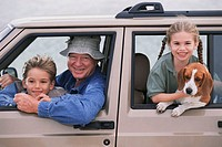 Portrait of a grandfather smiling with his grandson and granddaughter in a car