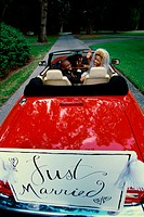 Portrait of a newlywed couple waving from a convertible car