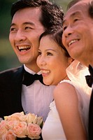Close-up of a newlywed couple smiling with a mature man