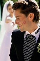 Close-up of a groom with lipstick marks on his cheek