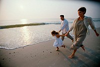 Parents running with their daughter on the beach