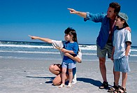 Young couple pointing on the beach with their son and daughter