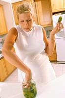 Pregnant woman taking pickles from a jar