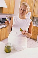Portrait of a pregnant woman eating pickles