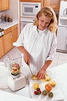Pregnant woman cutting fruit