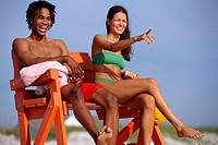 Young couple sitting on a lifeguard chair on the beach