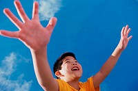 Low angle view of a boy with his arms outstretched