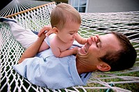 Father lying in a hammock with his baby boy