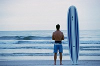 Rear view of a young man holding a surfboard standing on the beach