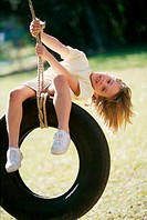 Portrait of a girl sitting on a tire swing