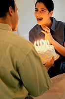 Mid adult man holding a birthday cake in front of a mid adult woman