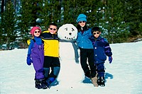 Portrait of a group of children standing near a snowman