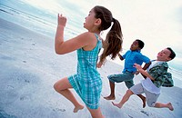 Side profile of a girl and two boys running on the beach
