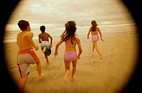 Rear view of a group of children running on the beach
