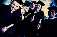 Portrait of a group of young graduates holding diplomas smiling