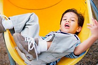 Portrait of a boy lying on a slide