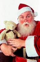 Portrait of Santa Claus holding a teddy bear