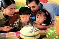 Son and daughter blowing out candles on their birthday cake with their parents behind them