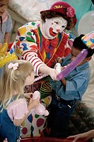 High angle view of a clown playing with children at a birthday party