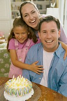 Parents with their daughter in front of a birthday cake